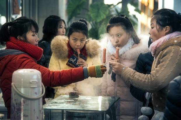 Schoolgirls buy hot dogs on a stick from a street vendor outside a skating rink. Teenaged social life plays out here in much the same way as anywhere, with cliques converging en masse on Pyongyang's leisure centres and its few department stores every day after school gets out.