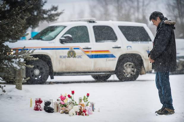 Cody Montgrand leaves a prayer candle at a makeshift memorial for the victims of the La Loche school shooting.