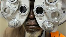 An South African man has his eyes tested inside the Phelophepa medical train at the rural Kirkwood railway station in Eastern Cape province on Jan. 24, 2006. (DENIS FARRELL/AP)