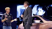 Johan De Nysschen, President of Infiniti, talks with German Formula One racing driver Sebastian Vettel (L) during the presentation of an Infiniti Q30 concept car during a media preview day at the Frankfurt Motor Show on September 10, 2013. (KAI PFAFFENBACH/REUTERS)