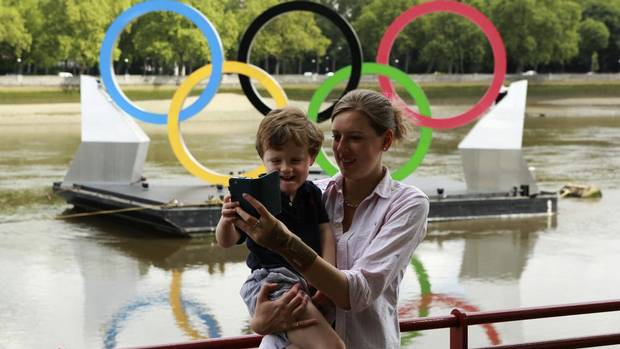Jo shows Arthur, 3, a picture of himself in front of the Olympic Rings on the River Thames at Battersea in central London July 21, 2012. (OLIVIA HARRIS/Reuters)