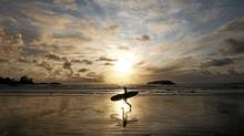 A surfer heads home after catching a few waves at North Chesterman Beach in Tofino, BC, November 4, 2011. (John Lehmann/The Globe and Mail/John Lehmann/The Globe and Mail)