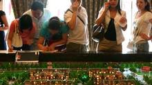 Customers view models of apartment blocks during a sales promotion activity in Chongqing, China. (China Photos/Getty Images)