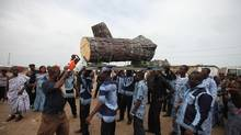 Eric Borketey, whom Mr. Laryea taught and mentored in the tree-cutter trade, brandishes a bladeless chainsaw as a sign of respect. Here, he has paused the pallbearers so that he can let the chainsaw reverberate against the coffin - which has been designed to resemble a cut-down tree. (Iain Marlow for the Globe and Mail)