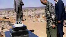 Former President Nelson Mandela and Orania Movement founder Carel Boshoff, right, inspect a statue of Apartheid prime minister Hendrik Verwoerd, during a visit to Orania, in this file photo taken August 15, 1995. While the death of anti-apartheid leader Mandela triggered an outpouring of shared sorrow across South Africa's sometimes tense racial divide, eyes stayed dry in the white Afrikaner enclave in the heart of the country. But even in Orania, where a small community of Afrikaners has closed itself off, intent on preserving its culture and language at all cost, the global icon who preached a contrasting ideology of racial integration commands respect. (JUDA NGWENYA/REUTERS)