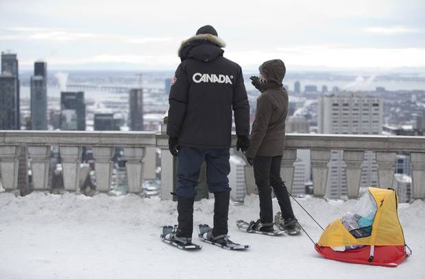 People look out at the city from Mont-Royal in Montreal. The skyline is becoming more crowded as new towers are erected.