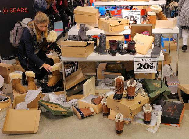 A shopper browses for boots at a Sears Canada location in Mississauga, Ont., on the first day of liquidation sales on Oct. 19, 2017.