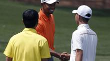 Asia-Pacific Amateur Championship winner, 14 year old Guan Tianlang of China, shakes hands with Tiger Woods during practice at Augusta National Golf Club (PHIL NOBLE/REUTERS)