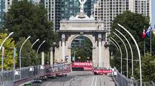 Driver Scott Dixon, right, of New Zealand drives on his way to winning first place past the Prince's Gates at the Honda Toronto Indy race in Toronto on Saturday July 13 , 2013. (Mark Blinch/THE CANADIAN PRESS)