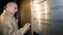 An Elections Canada official knocks on the door of Conservative Party headquarters in Ottawa on April 15, 2008 during an RCMP raid. (The Canadian Press)