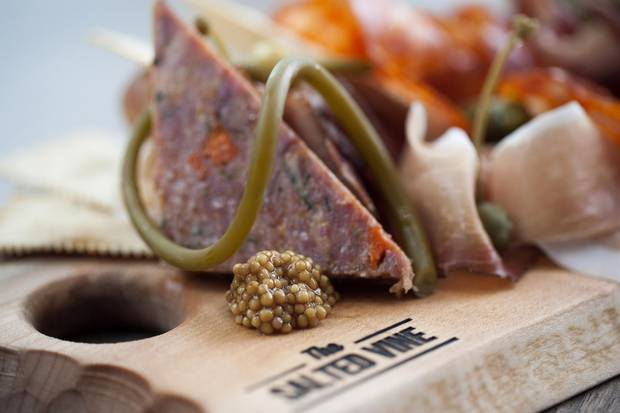 Assorted charcuterie with pickled mustard seeds and gherkins.