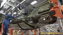 In this March 14, 2014 file photo, an assembly line worker works on a 2015 Chrysler 200 automobile at the Sterling Heights Assembly Plant in Sterling Heights, Mich. (Paul Sancya/AP)