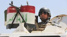 An Iraqi federal policeman standing on top an armored vehicle secures a checkpoint in Baghdad, Iraq on June 22. (Karim Kadim/The Associated Press)