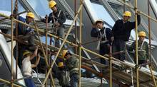 Workers stand on the scaffolding of a modern commercial building in Beijing in this file photo. (Ng Han Guan/AP Photo)