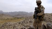 A Canadian soldier with the NATO-led International Security Assistance Force stands guard during a patrol at a hill top over looking Shah Wali Kot district some 35 km north of Kandahar Province on March 27, 2008. (SHAH MARAI)
