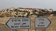 The West Bank Jewish settlement of Maale Adumim, near Jerusalem, is seen behind sign posts Dec. 3, 2012.) (AMMAR AWAD/REUTERS)