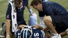 Toronto Argonauts quarterback Ricky Ray, centre, is helped by Argonauts medical trainers after he was injured while playing against the Calgary Stampeders during first half CFL football action in Toronto, on Friday, August 23, 2013. (NATHAN DENNETTE/THE CANADIAN PRESS)