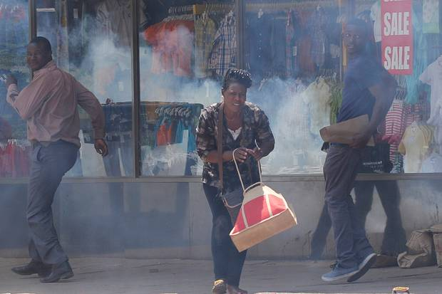 People flee tear gas during clashes between police and street vendors in central Harare on Sept. 27, 2016.