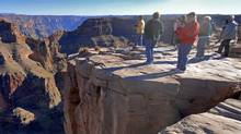 this Dec. 7, 2006 file photo, tourists visit the Hualapai Indian Reservation along the western end of the Grand Canyon. A new study published in the journal Science Thursday, Nov. 29, 2012, suggests the western Grand Canyon formed 70 million years ago. Some scientists disagree and believe the canyon was mainly carved by the Colorado River in the past 5 to 6 million years. (Jake Bacon/AP)