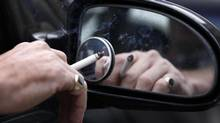A man smokes a cigarette as he sits in his car. The percentage of children in Canada under the age of 16 who reported being in a car with an adult smoking fell to 28 per cent in 2010 from 43 per cent in 2005, according to the Canadian Tobacco Use Monitoring Survey. (PHIL NOBLE/REUTERS)