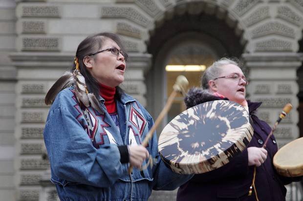 Marcia Brown Martel, left, drums outside court in Toronto on Dec. 1, 2016.