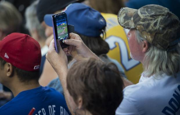 Top photo: Small cells, like those above the nosebleed section of the Rogers Centre, will play a key role in reliable 5G coverage. Bottom photo: Fans take in a Blue Jays game on September of 2017.
