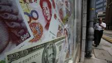 Photos of yuan (top) and U.S. dollar banknotes are displayed at a money exchange in Hong Kong Sept.13, 2010. The People's Bank of China has lowered banks' reserve ratio in an attempt to bolster lending. (BOBBY YIP/Reuters/BOBBY YIP/REUTERS)