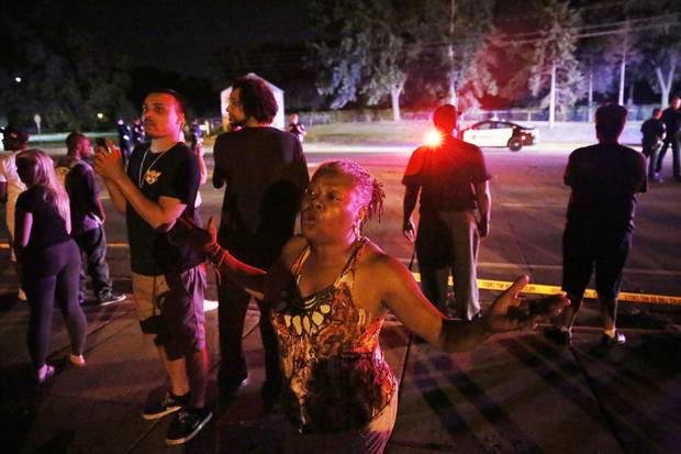 A woman joins others gathered at the scene of a police involved shooting on July 6, 2016, in Falcon Heights, Minn.
