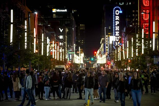 People fill Granville Street in Vancouver.