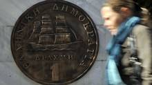 A woman walks by a monument in Athens representing the last Greek drachma coin. (LOUISA GOULIAMAKI/LOUISA GOULIAMAKI/AFP/GETTY IMAGES)