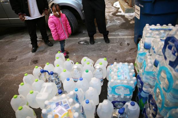 Jazmine Davis stands next to water cases and jugs of water that will be loaded onto a U-Haul truck for the people of Flint in Kalamazoo, Mich.