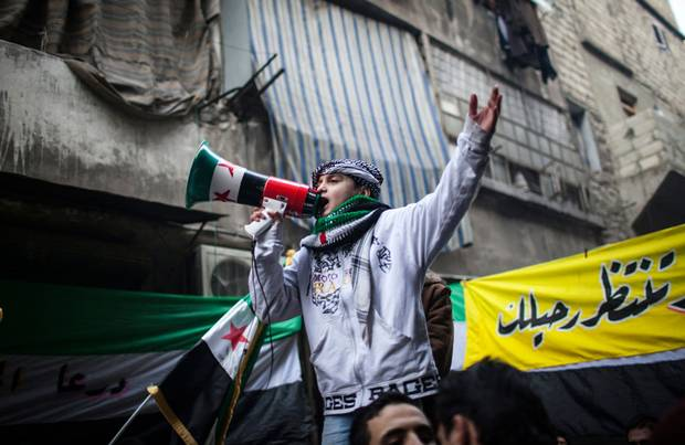 A child uses a megaphone to lead others in chanting Free Syrian Army slogans during a demonstration in the neighborhood of Bustan Al-Qasr, Aleppo, Syria, Friday, Jan. 4, 2013. By then, more than 60,000 people had been killed since Syria's crisis began in March 2011.