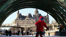 The historic hotel Château Laurier is framed through an arch of a bridge as skaters brave the cold weather to enjoy a day on the Rideau Canal in Ottawa Sunday, Jan. 25, 2004. (JONATHAN HAYWARD/CP)