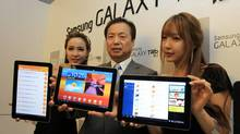 Shin Jong-kyun, president of Samsung Electronics' mobile communications business, center, and models show off the new tablet Galaxy Tab 10.1 during its unveiling in Seoul, South Korea, Wednesday, July 20, 2011 as the company launches the tablet computer on the South Korean market. (Lee Jin-man/AP)