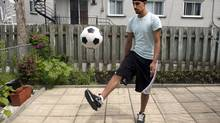 Aneel Samra, 18, plays with a soccer ball in his backyard, Wednesday, June 5, 2013 in Montreal.Samra has not been able to play organized soccer since last year due to his religious headgear. (Ryan Remiorz/THE CANADIAN PRESS)