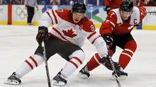 Canada's Sidney Crosby (L) with a nose injury drives to the net on Switzerland's Mark Streit during their men's preliminary round match at the Vancouver 2010 Winter Olympics February 18, 2010. (Olympics)