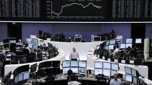 Traders work at their desks in front of the DAX board at the Frankfurt stock exchange July 10, 2012. (TOBIAS SCHWARZ/REUTERS)