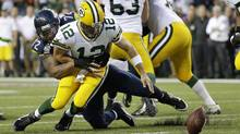 Green Bay Packers quarterback Aaron Rodgers fumbles after Seattle Seahawks' Michael Bennett knocked the ball loose in the second half of an NFL football game, Thursday, Sept. 4, 2014, in Seattle. (Associated Press)