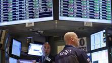 Traders work at the Knight Capital kiosk on the floor of the New York Stock Exchange. The market maker said a technology issue had affected the routing of shares of around 150 stocks to the New York Stock Exchange Wednesday, where abnormal volatility roiled the markets in early trading. (BRENDAN MCDERMID/REUTERS)
