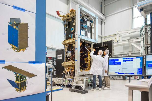 Flight assemblers install components in the satellite's bus module which will be fitted with a solar array and antennae before blast off