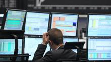 A trader reacts at his desk in front of the DAX board at the Frankfurt stock exchange on Monday. Euro zone blue chips turned positive by mid-session, bouncing back from oversold territory after a knee-jerk reaction to French and German elections. (ALEX DOMANSKI/REUTERS)