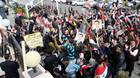 Syrians hold up their national flag and images of President Bashar al-Assad as they rally in front of the Foreign Ministery as their Foreign Minister Walid Muallem speaks to the press in the capital Damascus, on November 14, 2011.
