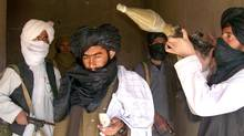 "A front-line Taliban commander in Sangin district of Helmand province (centre, with cellphone), who declined to give his name, said in a videotaped statement that the insurgents have recently caught ""60 or 70 spies,"" suspected informants for NATO. (for The Globe and Mail)"