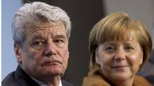 German Chancellor Angela Merkel (R) looks at former East German rights activist Joachim Gauck, joint candidate of government and opposition for the post of president, at the Chancellery in Berlin Feb. 19, 2012. (THOMAS PETER/REUTERS/THOMAS PETER/REUTERS)