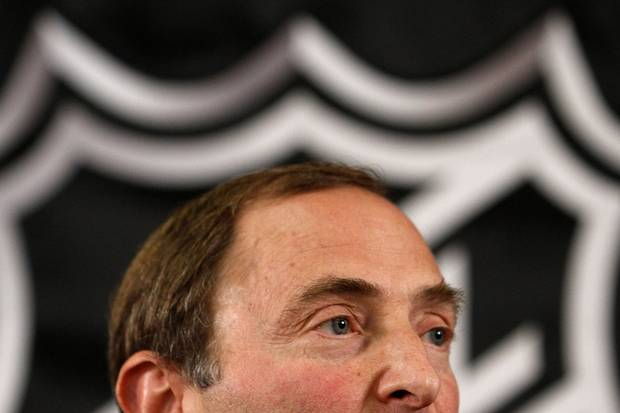 The NHL logo looms behind league commissioner Gary Bettman.