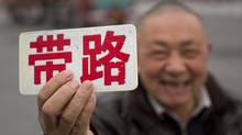"Pei Dian'ao a human map on the out skirts of Hangzhou, waves a sign marked ""Lead [you on the] Road"" as he waits for a customer at exit to the newly built industrial area of Hangzhou, China February 7, 2013. (John Lehmann/The Globe and Mail)"