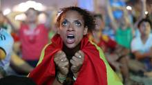 A Spain soccer fan reacts in frustration as she watches the live broadcast of the World Cup match between Spain and the Netherlands inside the FIFA Fan Fest area on Copacabana beach in Rio de Janeiro, Brazil, Friday, June 13, 2014. The Netherlands thrashed Spain 5-1 Friday. It was a humiliating defeat for the defending World Cup champions. (Leo Correa/AP)