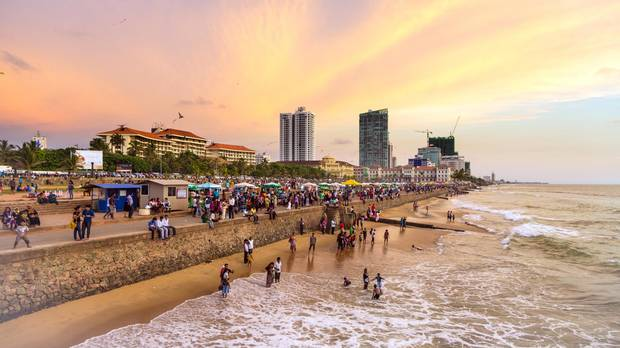 A large crowd enjoys the sunset on Galle Fort Road on the seafront of Colombo, the capital city of Sri Lanka.