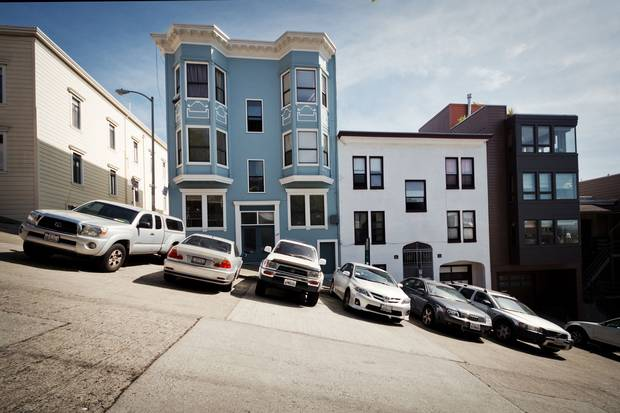 Cars park in a row on a steep San Francisco hill. San Francisco's experiments in the central business district and five neighbourhoods aim to secure free parking spots on every block.