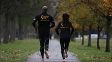 David Robinson and Anna Toombs run barefoot in a park in south London Dec. 1, 2011. (Stefan Wermuth/REUTERS)